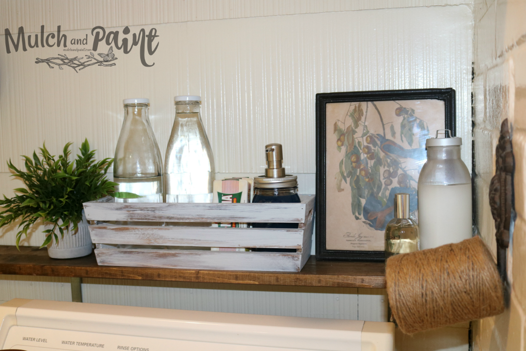 Laundry Room Makeover cleaning supplies on wooden shelf